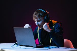Guy gamer winner with headset playing video games on his personal computer
